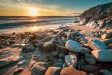 une plage avec des pierres en premier plan face à un coucher de soleil sur l'océan et des falaises