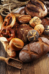 Different kinds of bread and bread rolls on board from above. Kitchen or bakery