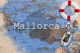 Maritime Dekoration auf blauem Holzuntergrund mit Umriß der Insel Mallorca und Beschriftung