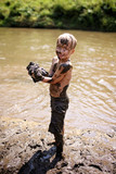 Muddy Little Boy Child Laughing as He Swims and Plays Outside in River - 223103022
