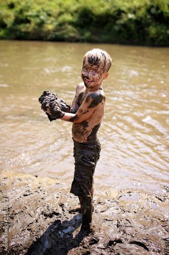 Foto Murales Muddy Little Boy Child Laughing as He Swims and Plays Outside in River
