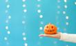 Woman holding a halloween pumpkin on a shiny light blue background