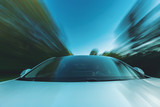Luxury vehicle driving down the road with motion blur