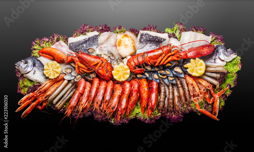 Fish plate / Creative concept photo of  sea food on plate on black background. - 223106030