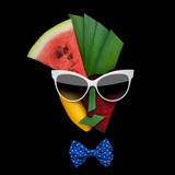 Tasty art / Creative concept photo of cubist style female face in sunglasses made of fruits and vegetables, on black background.