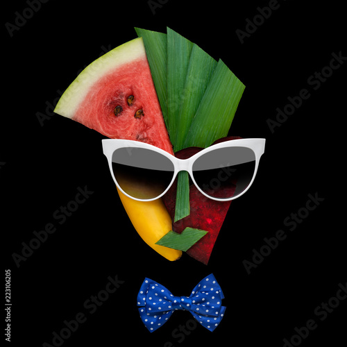 Tasty art / Creative concept photo of cubist style female face in sunglasses made of fruits and vegetables, on black background. - 223106205