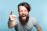 anger fury rage and accusation concept. bearded man screaming and blaming someone and pointing finger. emotional reaction and facial expression. hipster man portrait on blue background. - 223107277