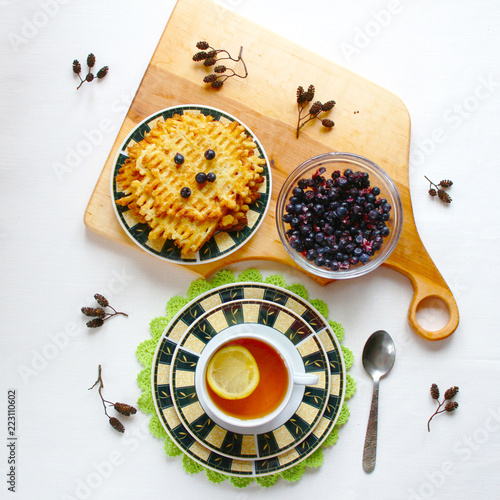 Wall mural Winter Breakfast on a white tablecloth. A plate of frozen blueberries, homemade cakes, waffles on a wooden serving Board, tea with lemon. The concept of rest, brunch, comfort.