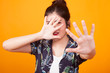Young Asian woman hide her  face in tropical shirt