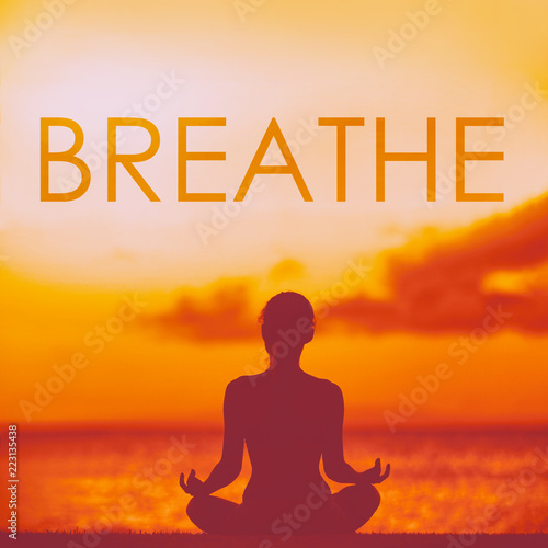 Leinwanddruck Bild BREATHE yoga inspirational title on beautiful beach with woman meditating doing yoga at sunset. Word breathe written on copy space for inspiration and motivation in health and fitness concepts.