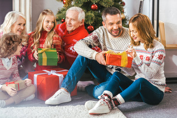 beautiful family with gift boxes sitting on floor of living room during christmas