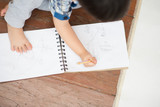 Little toddler boy draw pictures on a paper by use pencil - 223140020