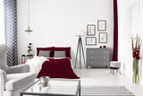 Glamour bedroom interior in white, gray and burgundy with a bed dressed in wine color linen. Lamp and drawer cabinet by the bed. Real photo. - 223146466