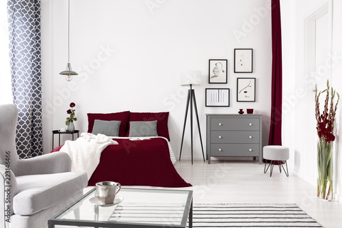 Glamour wnętrze sypialni w kolorze białym, szarym i bordo z łóżkiem ubrane w kolor wina. Lampa i szafka z szufladami przy łóżku. Prawdziwe zdjęcie.