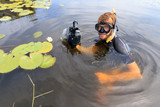 Very handsome young man in a river with water lilies in Rijpwetering, the Netherlands, with equipment for underwater photography on July 19, 2014 - 223150236