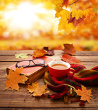 Autumn background. Autumn leaves, book and cup of tea on wooden table in park. - 223163693