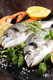 Delicious fresh fish. Fish with aromatic herbs, spices and vegetables - healthy food, diet or cooking concept. - 223165230