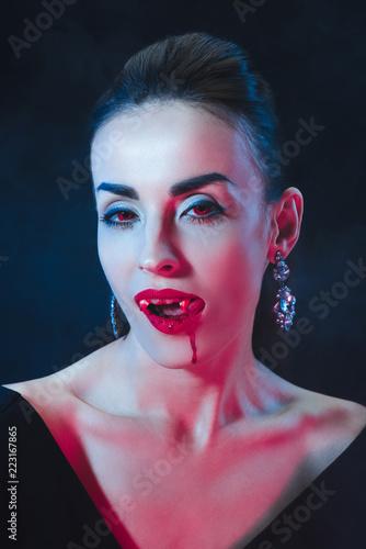 Sexy Vampire Woman Licking Her Lips On Dark Background