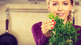 Woman holding green herb, parsley - 223172886