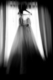 Wedding dress hanging in the window in black and white - 223178421