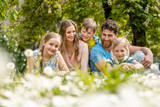 Family sitting on a meadow in summer or spring amidst dandelion flowers