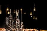 Anguille cotte allo spiedo sulla brace viva con lanterne e maialetti sullo sfondo - 223184608
