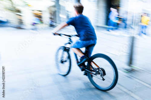 Poster bicycle rider in the city in motion blur