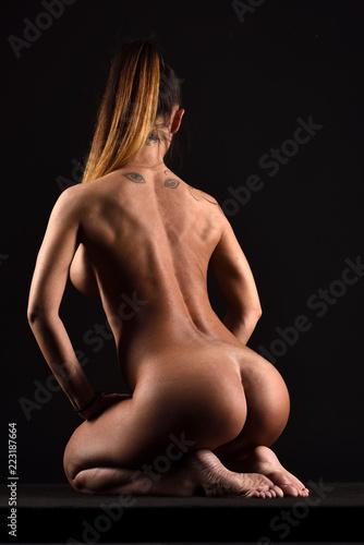 Nudo artistico di donna nuda ragazza erotica sexy e sensuale seduta in ginocchio con gambe culo schiena e piedi su fondo nero