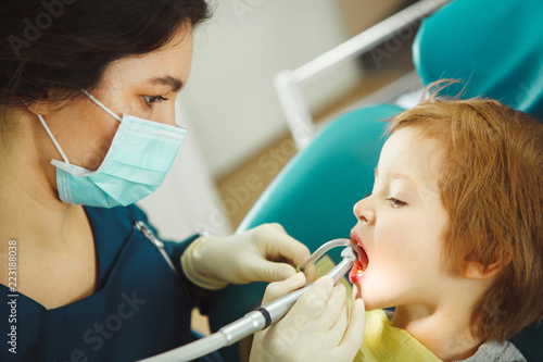 Female dentist drills the teeth of small child. Prevention of tooth decay. - 223188038