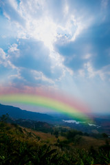 Landscape, mountain hill sun beam and lighting blue sky with rainbow. beautiful nature background and wallpaper.
