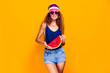 Beautiful young female in cap, sunglasses and swimsuit hold slice of watermelon and looking away while standing on yellow background. Copyspase