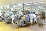 Arbeiter in einer Fleischerei bei der Herstellung von Würsten // Workers in a butcher's shop producing sausages  - 223193076