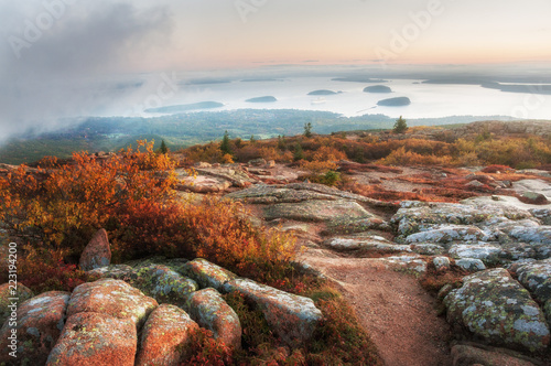 View from the top of the mountains at sunrise to the bay with sparks and the beautiful landscape of the Atlantic coast. Mount Cadillac. Acadia National Park. USA. Maine.
