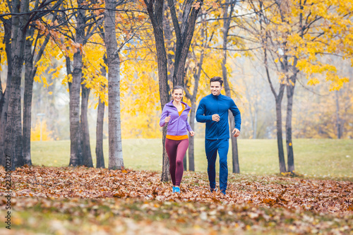 Leinwandbild Motiv Man and woman running as fitness sport in an autumn park with colorful foliage