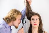 Man looking at woman hair through magnifer