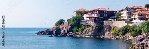 Panoramic photo of the cliff with houses and restaurants by the sea