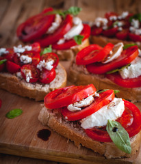 Close-up of bruschetta with cheese, tomatoes, fresh basil and balsamic vinegar on cutting board