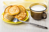 Pancakes in saucer, cup with milk, fork, yellow napkin - 223222644