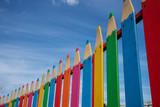decorative fence in the form of pencils against the blue sky - 223229407