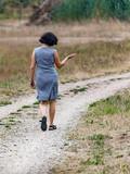 Woman is walking alone on dirt road