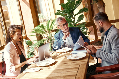 Naklejka Business lunch. Three people in the restaurant sitting at table brainstorming on project using digital devices. Team work concept