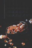 Brown candy cane sugar in bowl on black table, selective focus - 223264272