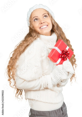 Leinwanddruck Bild Young Woman In Winter Clothes Holding Present - Isolated