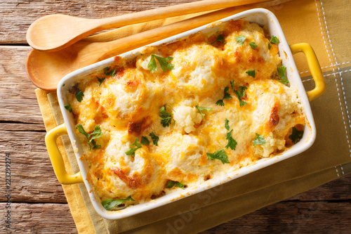 Fototapeta Delicious baked fresh cauliflower with cheese sauce close-up in a baking dish. horizontal top view