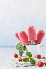 Homemade strawberry ice cream on wooden board over white background