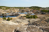 View on a flooded quarry with lakes and dried hills with rare vegetation. - 223306835