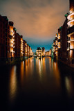 Hamburg, Germany. View of Wandrahmsfleet at dusk illumination light with clouds above. Located in Warehouse District - Speicherstadt Landmark of HafenCity quarter. Most visited touristic famous place - 223308234