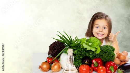 Leinwanddruck Bild Cute little girl with vegetables in kitchen