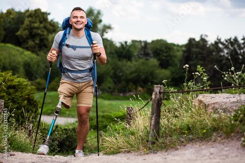 Fototapeta Overjoyed young man with prosthesis trying Nordic walking