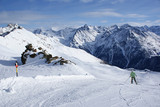 A man descends from the mountain in the Alps skiing with a steep slope